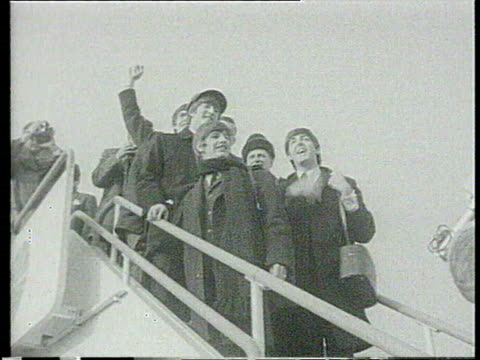 vidéos et rushes de legs of fans leaning over railing / the beatles boarding heathrow flight to new york / ws pan press surrounding plane / ms pan fans waving / ws plane... - 1964