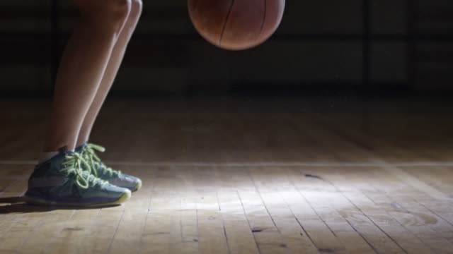 cu legs of female basketball athlete dribbling at court - bouncing stock videos & royalty-free footage