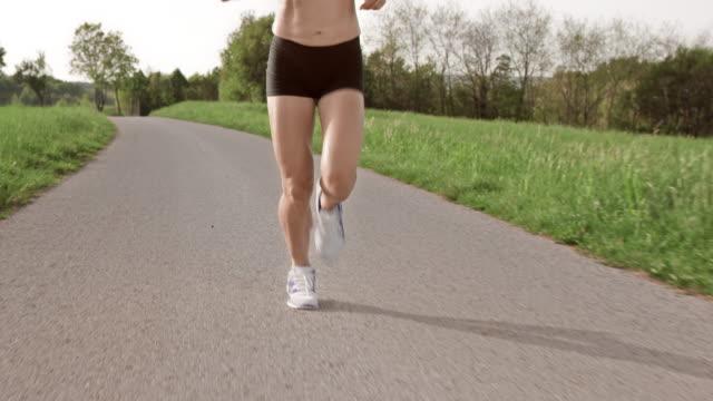 slo mo ts legs of female marathon runner on asphalt - human limb stock videos & royalty-free footage