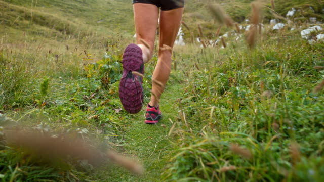 SLO MO Legs of female runner running across a meadow high in the mountains