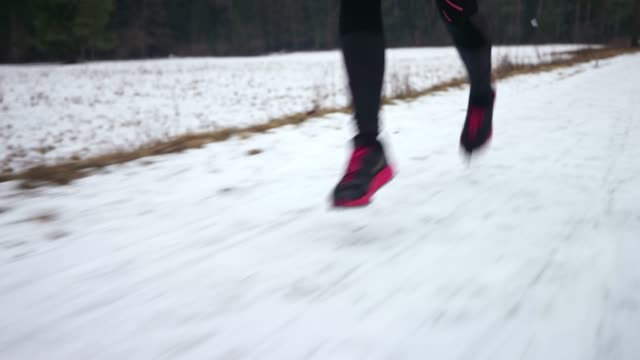 TS Legs of female runner running on a snowy surface on a cold day