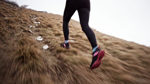 Legs of female runner running up a grassy mountain slope on a cloudy day