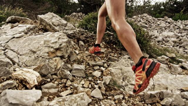 vídeos de stock, filmes e b-roll de slo mo pernas de corredor feminino subindo a montanha rochosa - colina acima