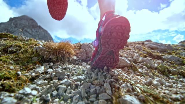 SPEED RAMP Legs of female runner scattering gravel on a mountain trail in sunshine