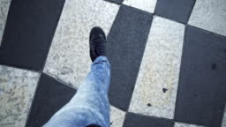 Legs of independent young man walking chessboard square, breaking rules, pov