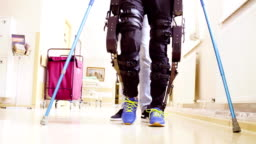 Legs of invalid in orthosis walking with support of two walking cane