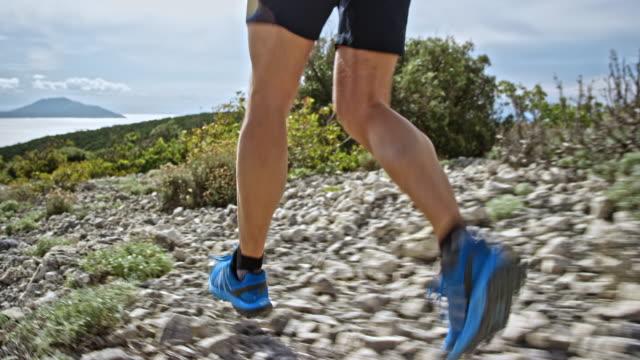 太陽の下で海の上の岩の歩道で実行されているオスの運動選手の足 - ツレス点の映像素材/bロール