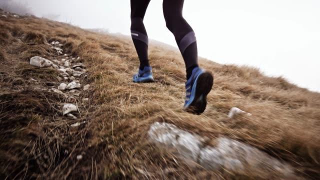 slo-mo-beine der männlichen läufer laufen auf einem grasbewachsenen berghang an einem bewölkten tag - off track laufen stock-videos und b-roll-filmmaterial