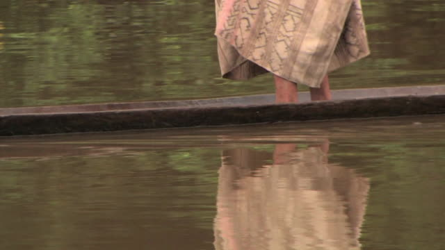 ms legs of man on river in narrow wooden raft/ manu national park, peru - minority groups stock videos & royalty-free footage