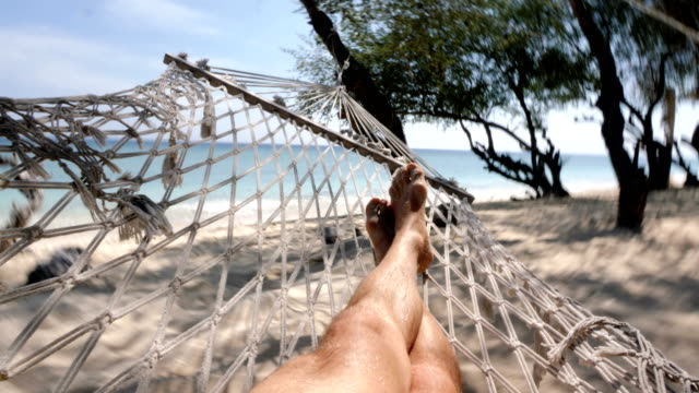 legs of man swinging at the beach in gili trawangan island in bali - audio available stock videos & royalty-free footage