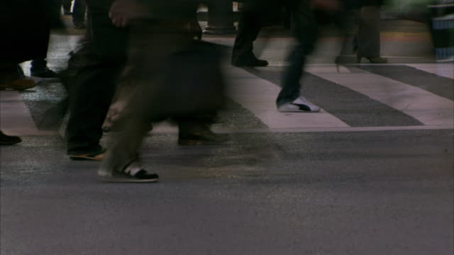t/l cu legs of pedestrians crossing street at night / tokyo, tokyo prefecture, japan - fußgänger stock-videos und b-roll-filmmaterial