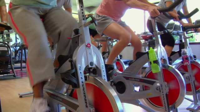 stockvideo's en b-roll-footage met ms legs of people pedaling stationary bikes in spin class/ tu woman in spin class/ san antonio, texas - cardiovasculaire training