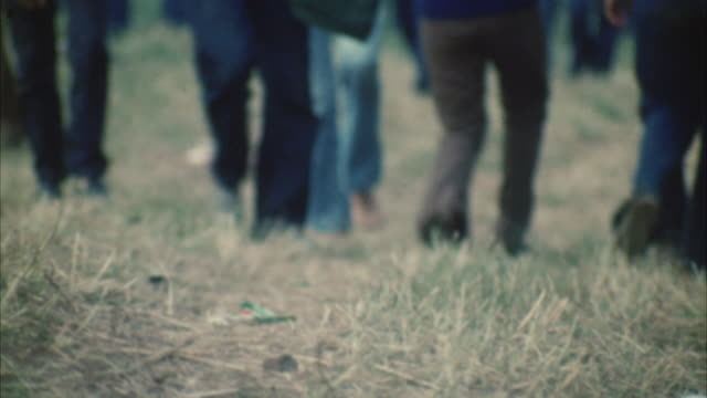 cu legs of people walking on grass at woodstock festival / bethel, new york, usa - anno 1969 video stock e b–roll