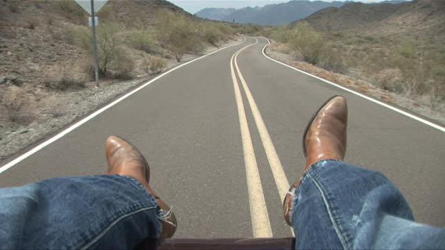 POV Legs of person in jeans and cowboy boots hanging off back of car while driving down desert road/ Scottsdale, Arizona