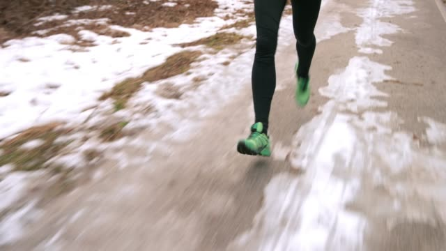 Legs of runner running on an icy surface