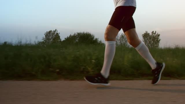 SLO MO TS pernas de senior runner correr ao pôr do sol