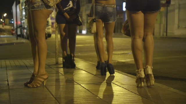 vídeos de stock, filmes e b-roll de legs of sex workers standing on street corner, medium shot - prostituta