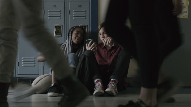 vidéos et rushes de legs of students passing lonely boy sitting on school corridor floor then smiling girl joining / provo, utah, united states - jeunes garçons