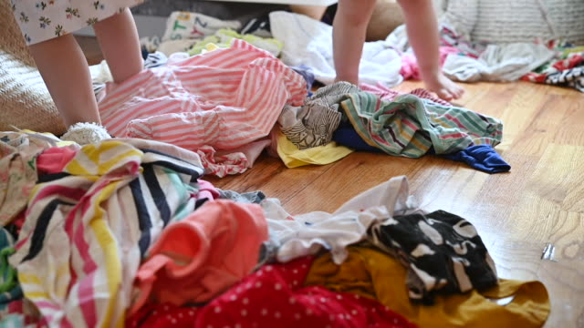 vidéos et rushes de legs of toddler sisters as they dance in pile of clothes on bedroom floor - messy bedroom