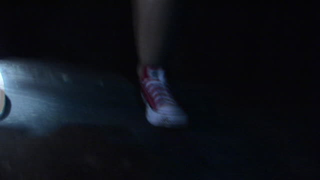 MS Legs of woman in shorts and sneakers writhing in front of blinking strobe light in old factory/ New York City