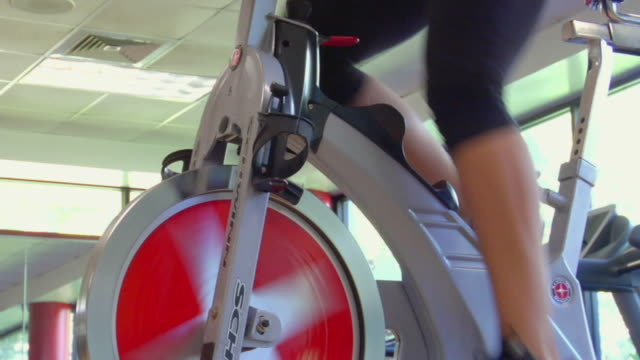 MS Legs of woman pedaling stationary bike in fitness club/ San Antonio, Texas