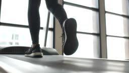Legs of Woman running on treadmill at the gym