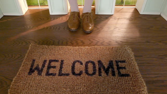 Legs of woman stepping on welcome mat