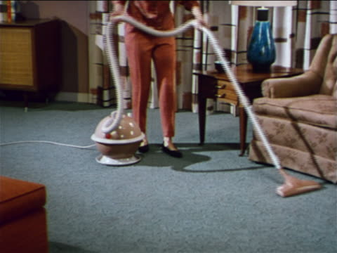 1962 legs of woman vacuuming rug with bulb-shaped vacuum cleaner / industrial