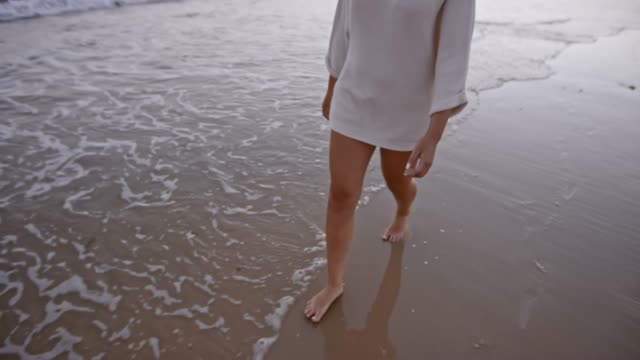 slo mo legs of woman walking on sandy beach at sunset - low section stock videos & royalty-free footage