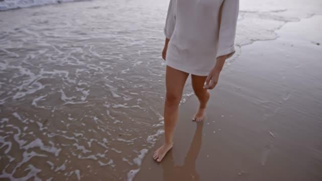 vídeos y material grabado en eventos de stock de slo mo piernas de mujer caminando por la playa al atardecer - parte inferior