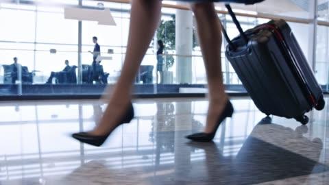 vídeos de stock, filmes e b-roll de pernas de mulher de salto alto andando no aeroporto com a bagagem com rodas - mala de rodinhas