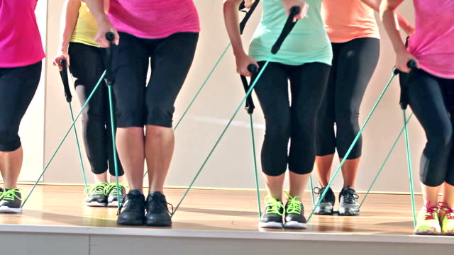 Legs of women in exercise class using resistance bands