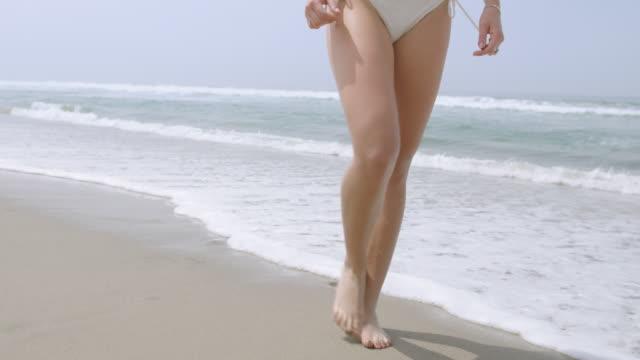 legs of young woman in white bikini walking on beach 4k - vesper stock stock videos & royalty-free footage