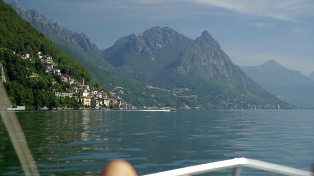 pov of legs on motorboat, looking out at view of lake and mountains - motorboat stock videos and b-roll footage