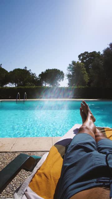 vidéos et rushes de jambes relaxantes pov: jambes croisées vue par une piscine pendant une journée ensoleillée d'été - boomerang