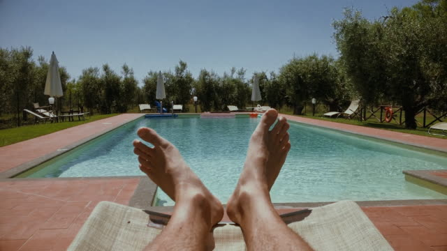 vídeos de stock e filmes b-roll de legs relaxing point of view: in a swimming pool - apanhar sol