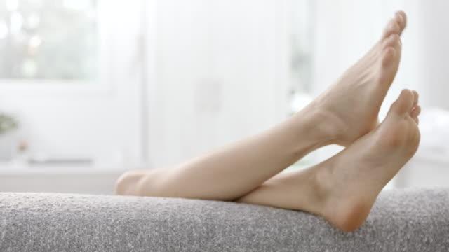 vídeos de stock, filmes e b-roll de pernas acima na parte de trás do sofá - de pé para cima