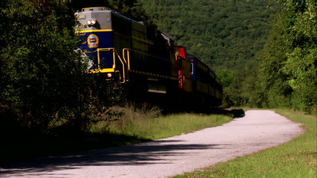 Lehigh Gorge Scenic Railway locomotive train passenger cars moving on railroad trees around road along rails Lehigh Gorge State Park PA