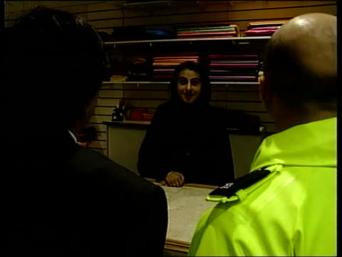 police officer along into shop as speaking to asian shop manager bv police officer and manager speaking to asian sales assistant behind shop counter... - jack straw stock videos & royalty-free footage