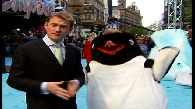 leicester square premier of 'happy feet' person in penguin costume dancing pull out reporter to camera - flightless bird stock videos & royalty-free footage