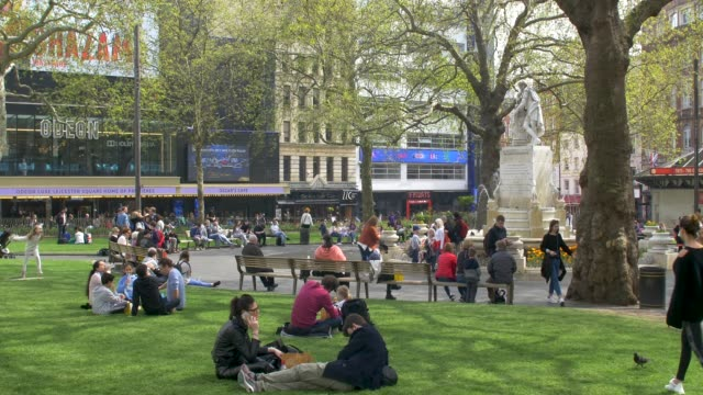 leicester square with fountain and statue of william shakespeare.tourists relaxing in the park. - leicester square stock videos & royalty-free footage