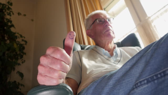 leisure at home cinemagraphs: senior man with quirky thumb - senioren männer stock-videos und b-roll-filmmaterial
