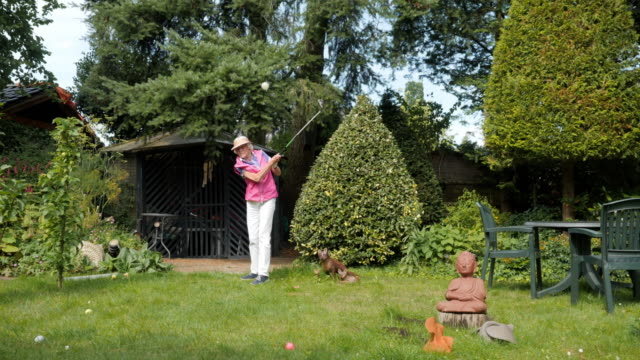 leisure at home cinemagraphs: senior woman practicing her golf swing - senior golf swing stock videos & royalty-free footage