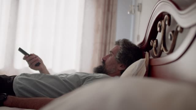 leisure at home. handsome mature man watching tv in bed during covid-19. holidays lifestyle. relaxing on vacations. - remote control stock videos & royalty-free footage