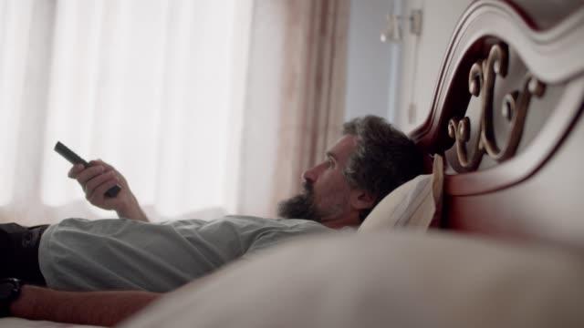 stockvideo's en b-roll-footage met vrije tijd thuis. knappe rijpe mens die tv in bed tijdens covid-19 let. vakantie levensstijl. ontspannen op vakanties. - afstandsbediening