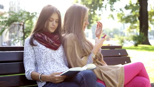 vidéos et rushes de loisirs avec un téléphone portable et livre - banc
