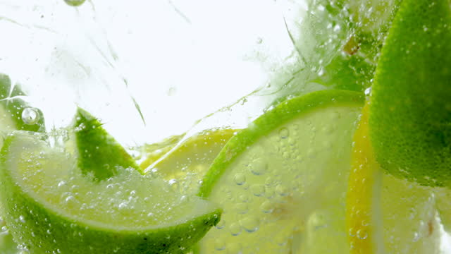 vídeos de stock, filmes e b-roll de limão e linha gota em água com gás efervescente, refresco de suco - frio