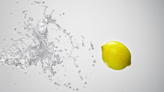 SLO MO Lemon being hit by a water splash in the air