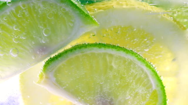 lemon drop in fizzy sparkling water, juice refreshment - lemon stock videos & royalty-free footage