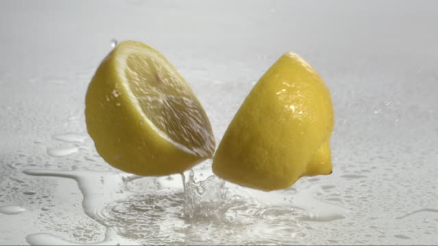 vídeos de stock e filmes b-roll de lemon falling and creating splashing droplets - dois objetos